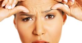 Frau überprüft Falten auf der Stirn